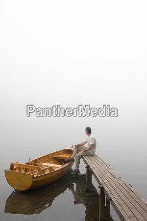 mann sitzt auf bootsteg im nebel