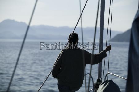 person auf segelyacht gegenlicht fjord