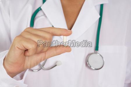 doktor mit uniform haelt eine pille