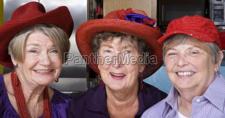 three senior women wearing red hats