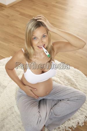 schwangere frau mit fieberthermometer