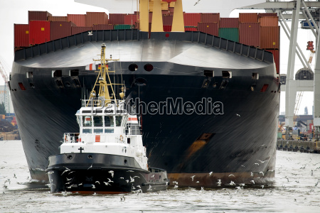tugboat towing freighter in harbor