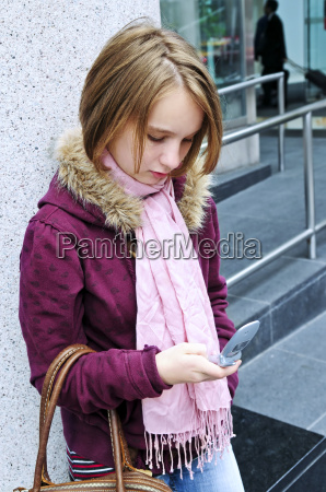 teenage girl text messaging on cell