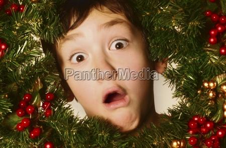boy in einem weihnachtskranz