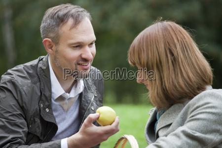 man gives a woman apple