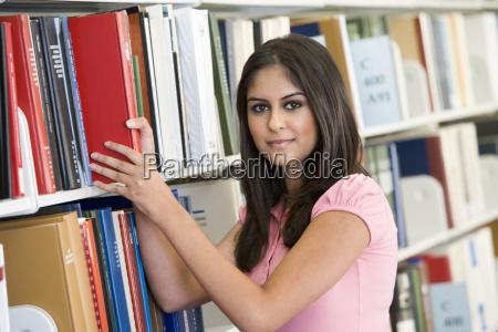 frau in der bibliothek ziehen buch