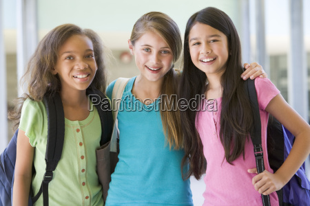 three students standing outside school together
