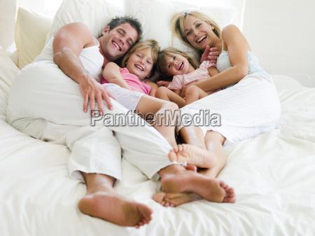 familie im bett liegend laechelnd