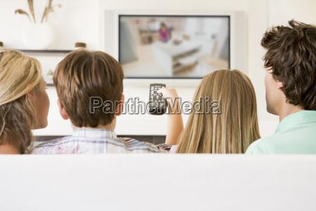 familie im wohnzimmer mit fernbedienung und
