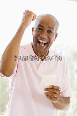 mann mit dem gewinn lotterielos aufgeregt