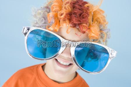 tragendes clownperuecke und sonnenbrillenlaecheln des jungen