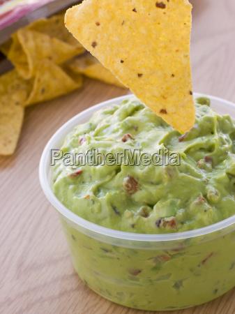 pot of guacamole mit einem mais
