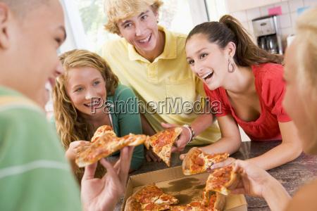 gruppe jugendlichen die pizza essen