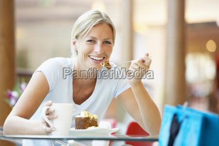 frau isst ein stueck kuchen auf