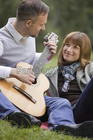 man plays guitar woman listens