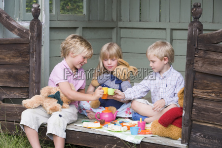 three young children in shed playing