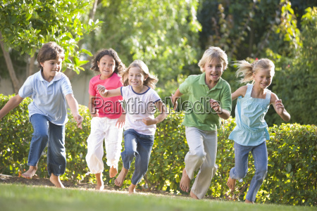 five young friends running outdoors smiling
