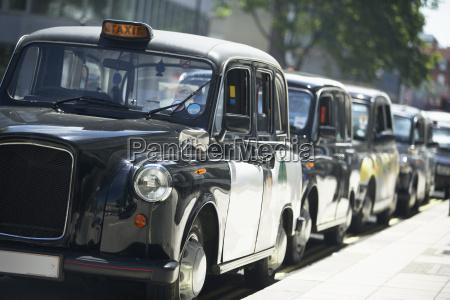 london taxis aufgereiht auf buergersteig