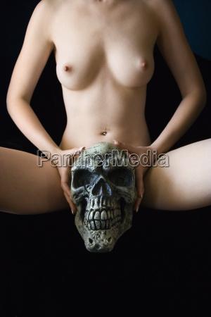 nude woman holding skull