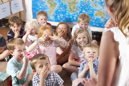 montessori pre school class listening to
