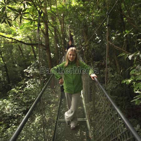 young girl posing on suspension bridge