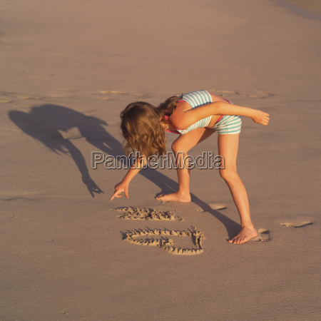 girl writing in the sand on