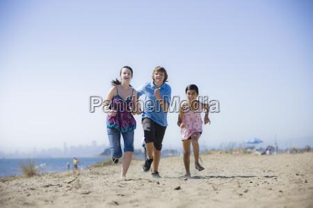 drei kinder die auf strand laufen