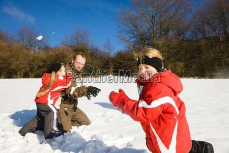 familie tobt im winter im schnee