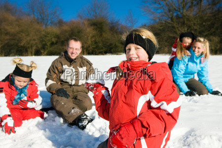 familie im schnee mit schneebaellen