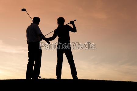 aelteres paar beim golfen im sonnenunterg
