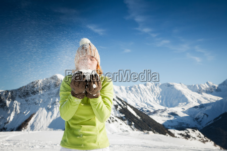 woman blowing on snow