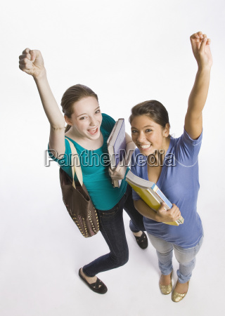 students carrying books and cheering