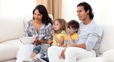 laechelnd familie vor dem fernseher auf
