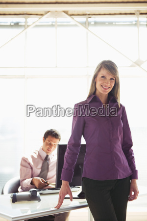 business woman smiling male colleague working
