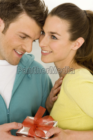 young couple holding gift close up