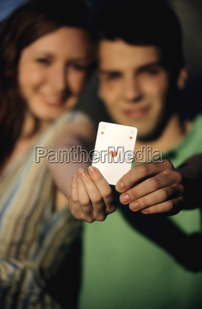 young couple showing ace of hearts