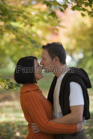 man kissing womans nose side view