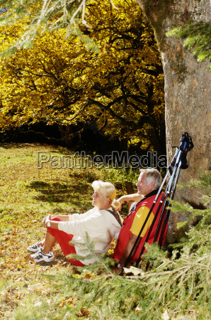 senior couple sitting in meadow man