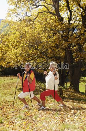 senior couple holding hiking pole exercising