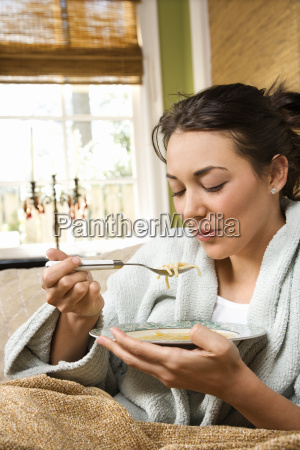 junge frau isst suppe