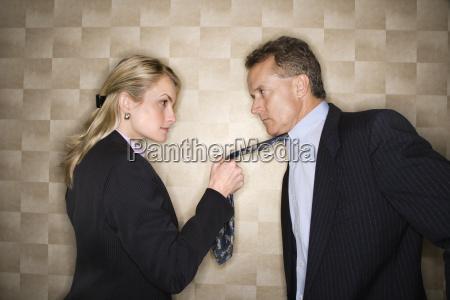 wuetende geschaeftsfrau zieht mann an den