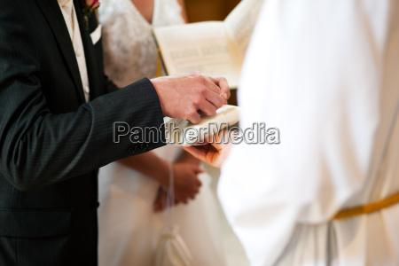 groom taking rings in wedding