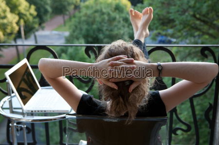 junge frau entspannt auf dem balkon