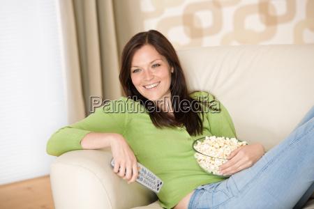 frau zeigt mit tv fernbedienung