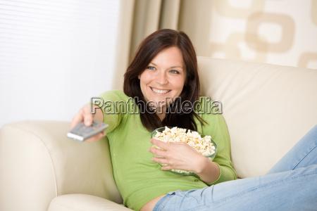 frau vor dem fernseher mit popcorn