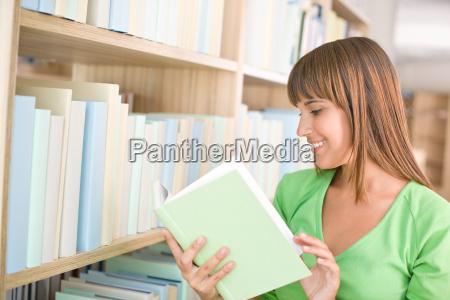 student in der bibliothek glueckliche