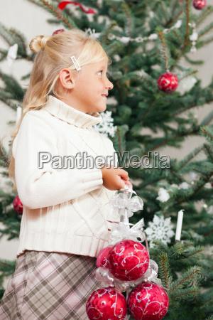child decorates the christmas tree