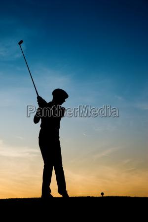 AEltere golfspielerin als silhouette