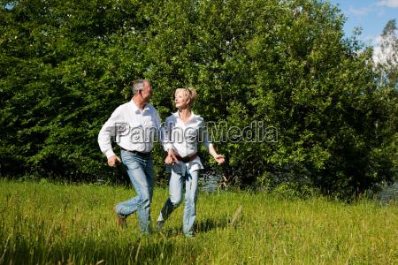 elderly couple running through a meadow