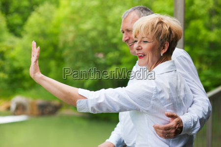 elderly couple on bridge waving